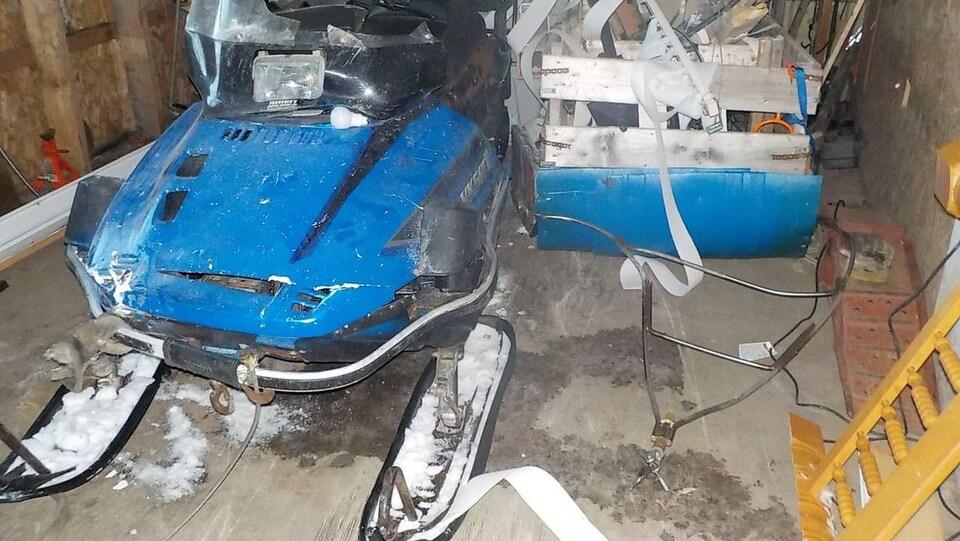 La motoneige endommagée dans une remise.
