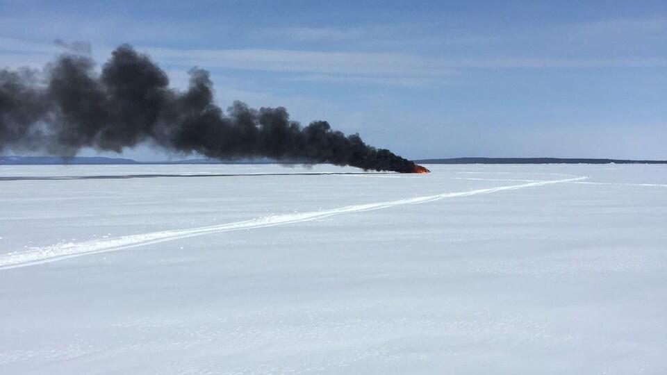 Un panache de fumée noire se dégage du lieu de l'incendie au milieu d'un lac gelé.