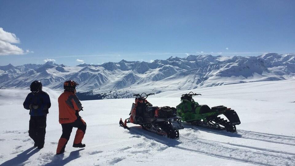 Deux motoneigistes debout dans la neige près de leurs machines sous un ciel dégagé. En arrière-plan, des montagnes couvertes de neige.