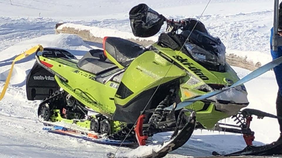 Une motoneige tirée par un câble sur la neige.