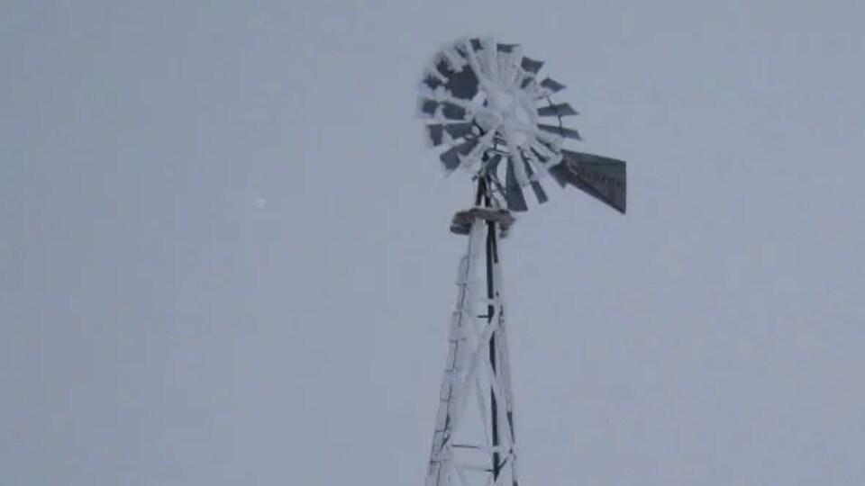 Un moulin à vent enneigé dans un champ.