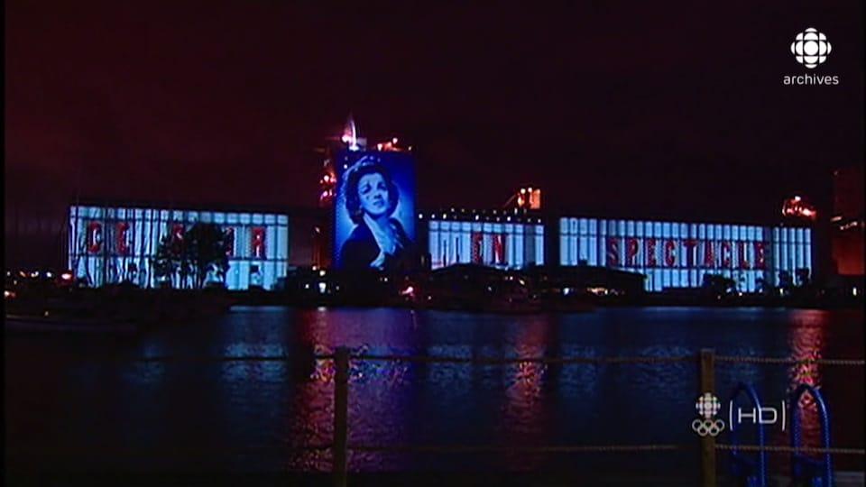 Les silos du bassin Louise dans le Vieux-Port de Québec sont illuminés avec l'image de la chanteuse Alys Robi et les mots «Ce soir en spectacle».