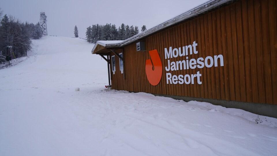 Un bâtiment au pied d'une pente de ski.