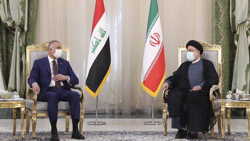 Moustafa al-Kazimi et Ebrahim Raïssi en conférence de presse conjointe, devant leurs drapeaux respectifs.