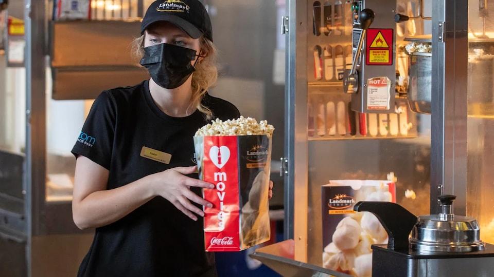 Une personne portant un max sur le visage et un sac de maïs soufflé dans les mains.