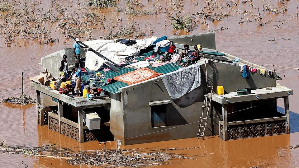 Une famille coincée sur le toit de sa maison dans le district de Buzi près de Beira, au Mozambique.