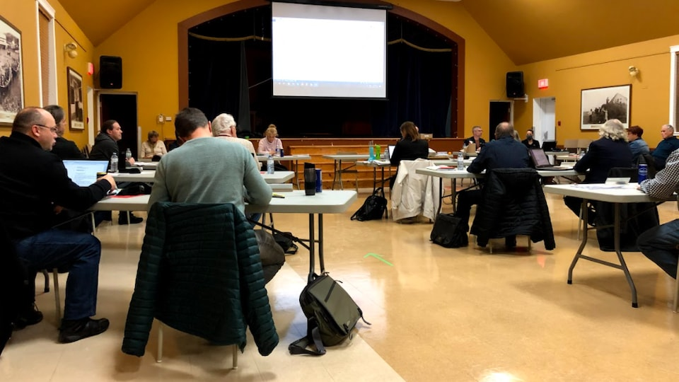 Les participants au conseil des maires sont assis à bonne distance les uns des autres dans une grande salle communautaire.