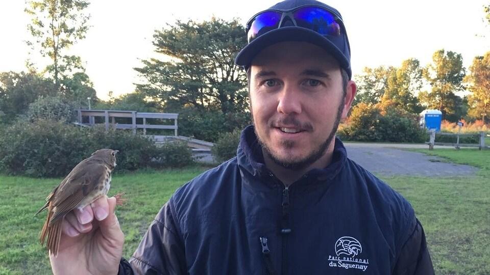 Pascal Côté tient un oiseau dans sa main et il sourit à la caméra.