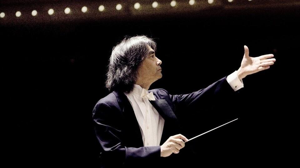 Le chef d'orchestre regarde vers ses musiciens et musiciennes, un bras en l'air, et l'autre tenant sa baguette.