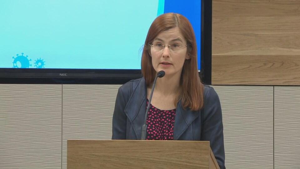 Cristin Muecke s'adresse aux journalistes dans une petite salle de conférence.