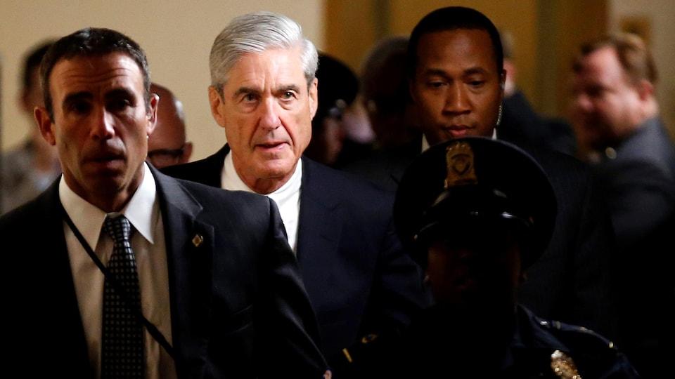 L'homme aux cheveux gris et portant un veston et une cravate marche dans un corridor entouré de plusieurs agents de sécurité.
