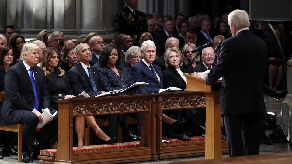 Un homme prononce un éloge devant une rangée de dignitaires assis dans une cathédrale.