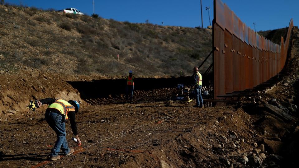 Des travailleurs de la construction travaillent sur une portion du mur entre San Diego et Tijuana le 13 décembre 2018.