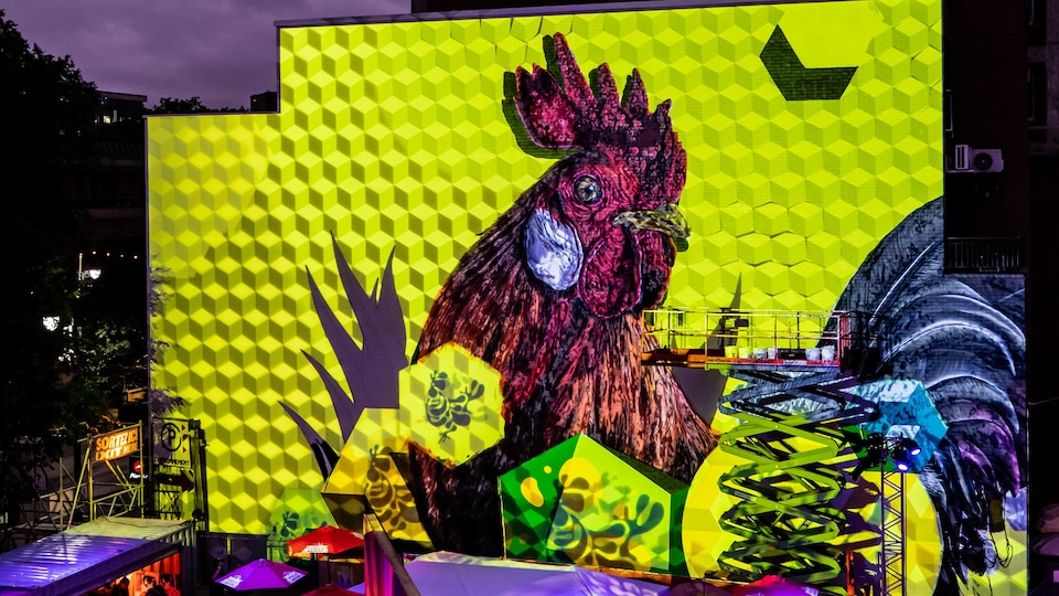 Une murale représente un coq sur un fond jaune.