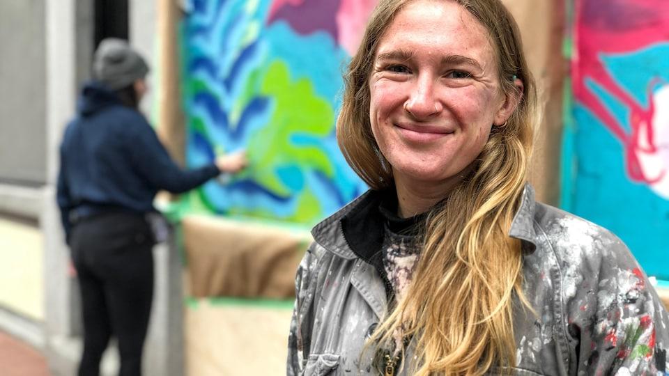 L'artiste Olivia Knight pose souriante devant sa murale.