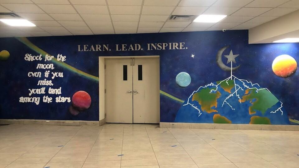 Une murale sur laquelle il est inscrit en anglais ''Apprendre, diriger, inspirer'' et ''Visez la lune, même si vous la ratez, vous atterrirez parmi les étoiles'' avec les planètes du système solaire en arrière-plan.