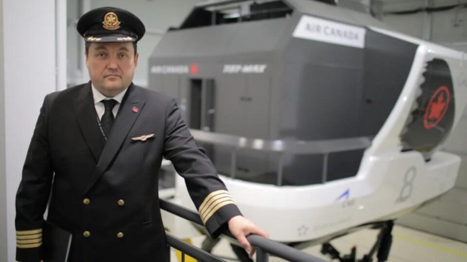 Un homme en tenue de pilote devant une machine au logo d'Air Canada.