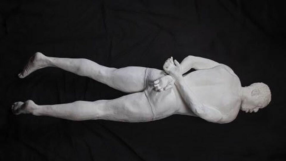 Sculpture d'un homme noir à plat ventre, les mains liées derrière le dos.