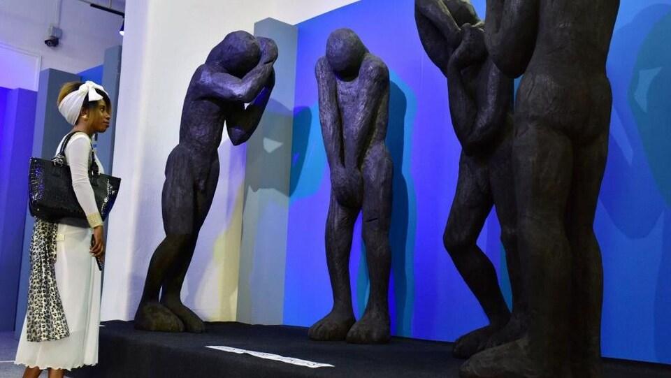 Une visiteuse regarde 4 grandes statues noires représentant des hommes.