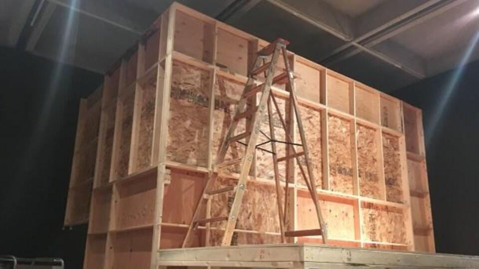 Un escabeau est placé sur une structure en bois et contreplaqué.