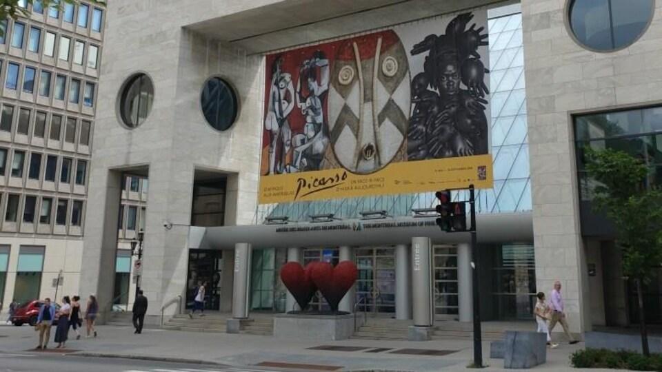 Image montrant la devanture d'un édifice du Musée des beaux-arts de Montréal, avec une grande affiche publicitaire faisant la promotion de l'exposition D'Afrique aux Amériques: Picasso en face-à-face, d'hier à aujourd'hui.
