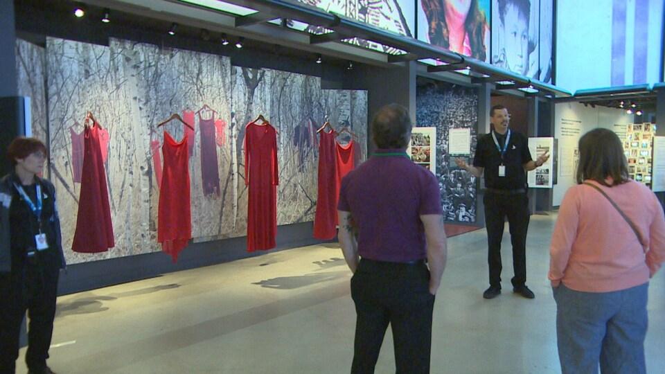 Un guide devant une galerie où sont exposées plusieurs robes rouges. Devant lui, des visiteurs écoutent.