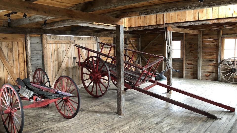 On voit des charrettes du début du dernier siècle dans un garage tout en bois.