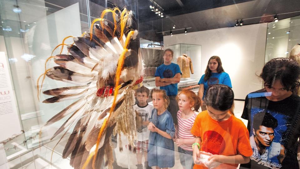 Des enfants observent une coiffe autochtone traditionnelle derrière la vitre d'un musée.