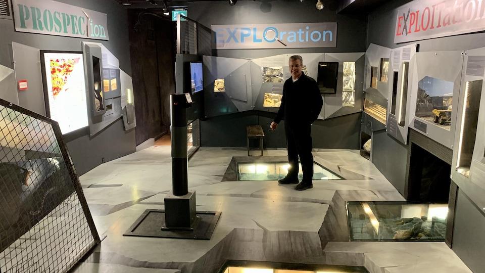 Un homme se tient debout dans une salle d'exposition minière.
