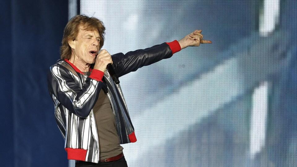 Un homme chante dans un micro et porte un bras dans les airs sur scène.