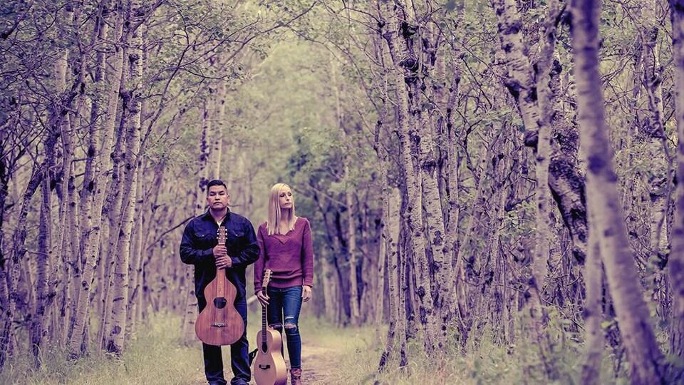 Un couple debout dans les bois, et tenant des guitares à la main.