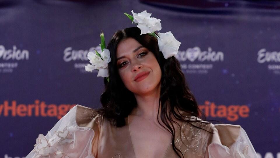 La chanteuse Katerine Duska vêtue d'une robe beige et portant trois fleurs blanches dans les cheveux.