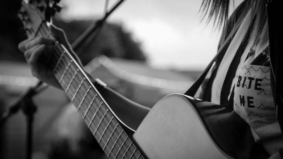 Une personne joue de la guitare.