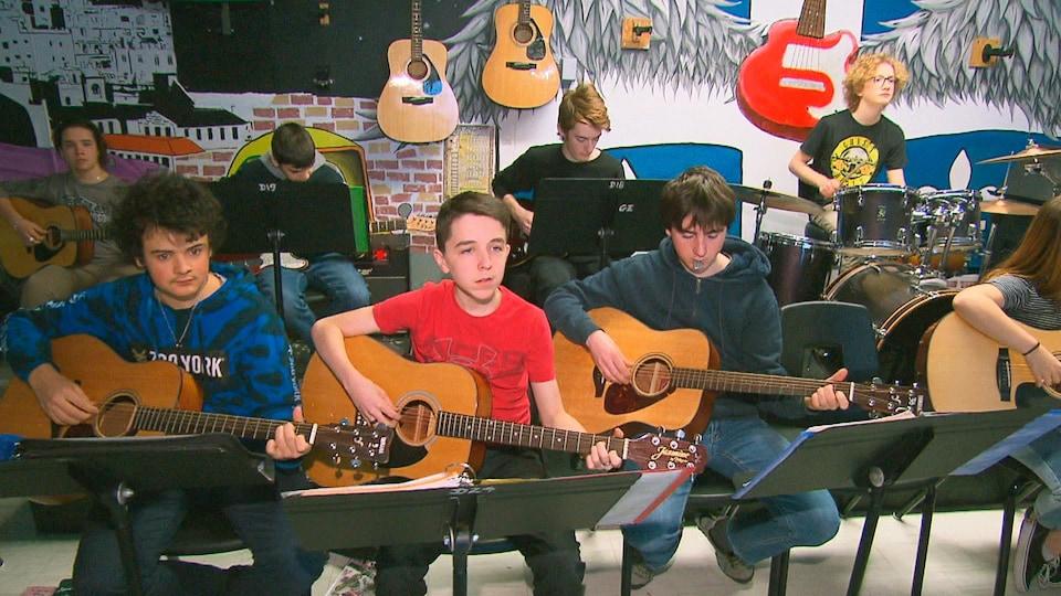Des jeunes pratiquent la guitare.
