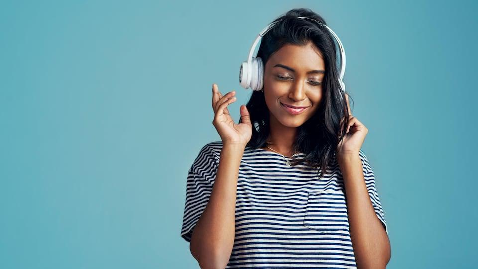 Une jeune femme qui écoute de la musique.