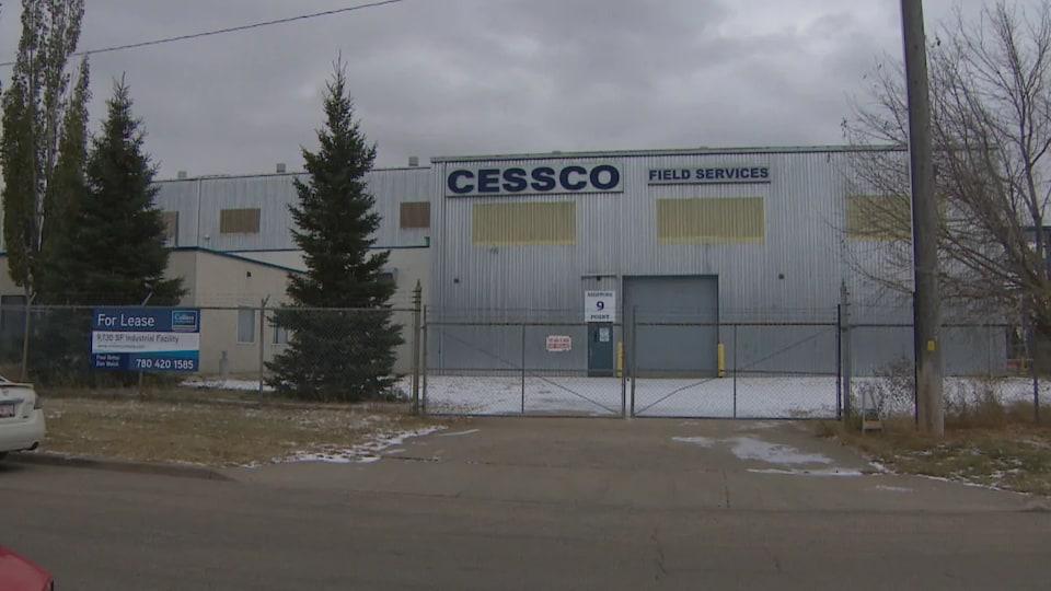 Un hangar fermé avec un panneau « à louer » accroché sur le grillage devant.