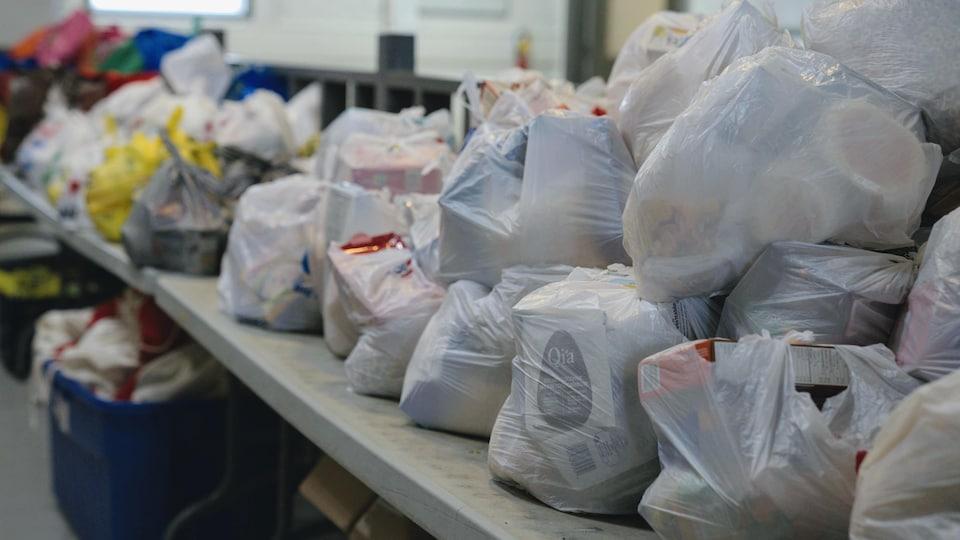 Des sacs de plastique contenant des dons pour les plus démunis sont sur une longue table.