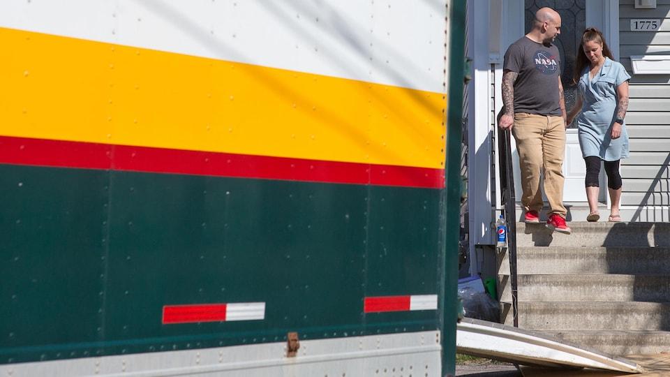 Sébastien Faubert et Cynthia Leroux se dirigent vers le camion de déménagement devant leur maison.