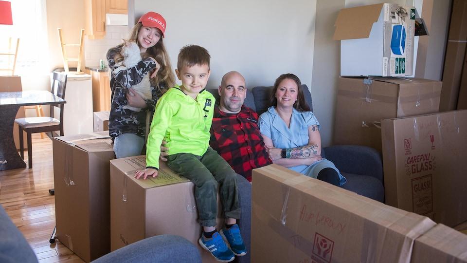 La famille assise dans le salon entourée de boîtes dans la maison du quartier militaire de Bagotville avant le déménagement.