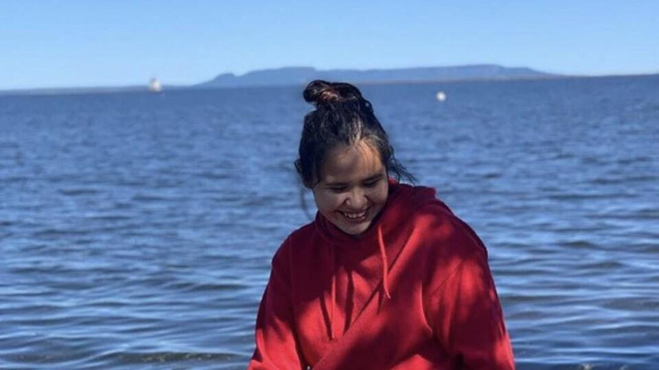 Mya Dixon est assise sur un rocher. Elle sourit les yeux baissés vers le sol. En arrière-plan, apparaît au loin la silhouette de montagnes et l'eau de lac tel un océan.