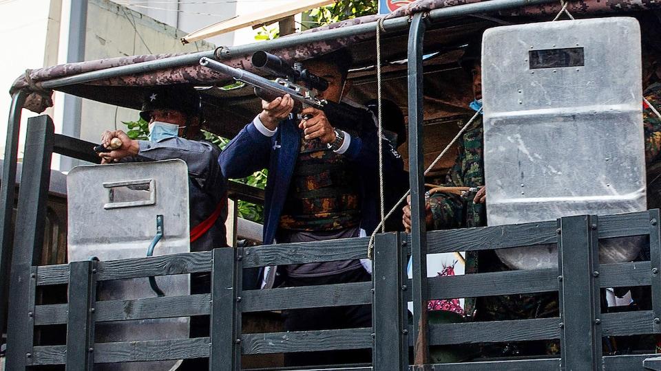 Un soldat du Myanmar pointe une arme, prêt à tirer.