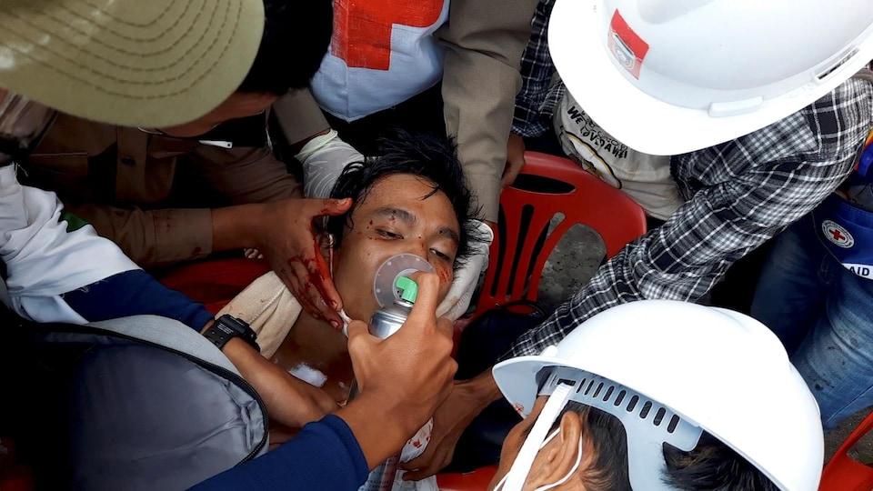 Des travailleurs de la santé tentent de soigner un homme blessé.