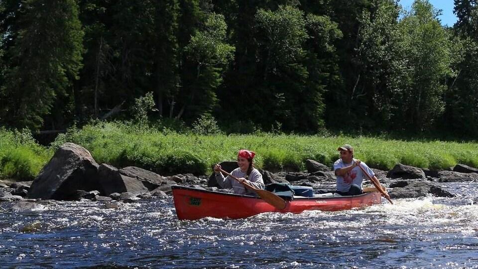 Un père et sa fille sur une rivière.
