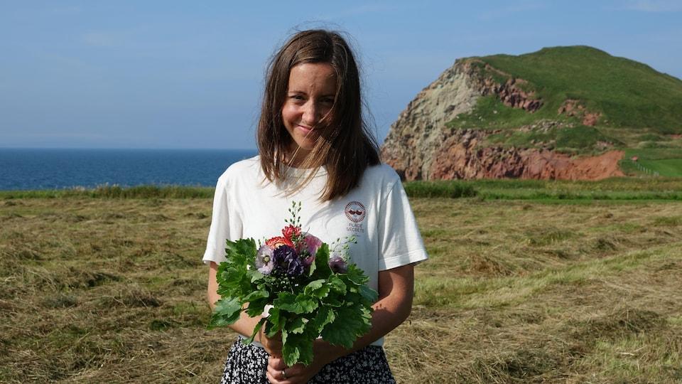 Mylène Montplaisir est photographiée devant un paysage madelinot avec un bouquet de fleurs dans les mains.