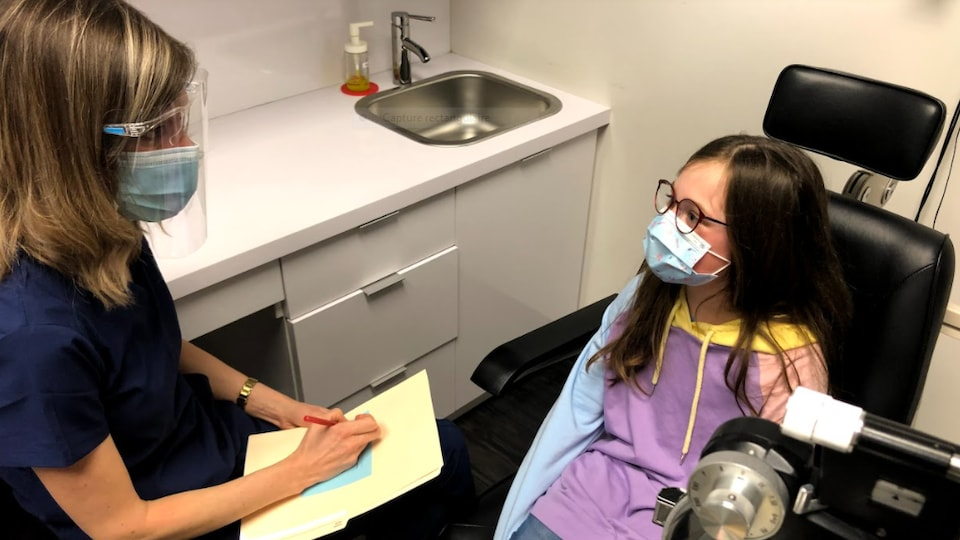 Une optométriste et une enfant portant des lunettes.