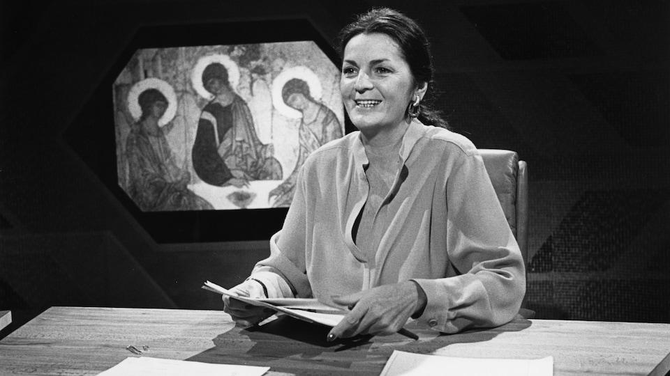 Myra Cree anime l'émission, une mortaise religieuse à l'arrière-plan.