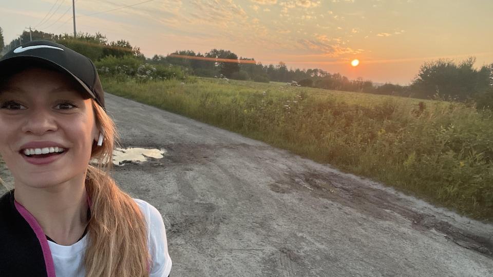 Une femme sourit à la caméra devant un lever de soleil.