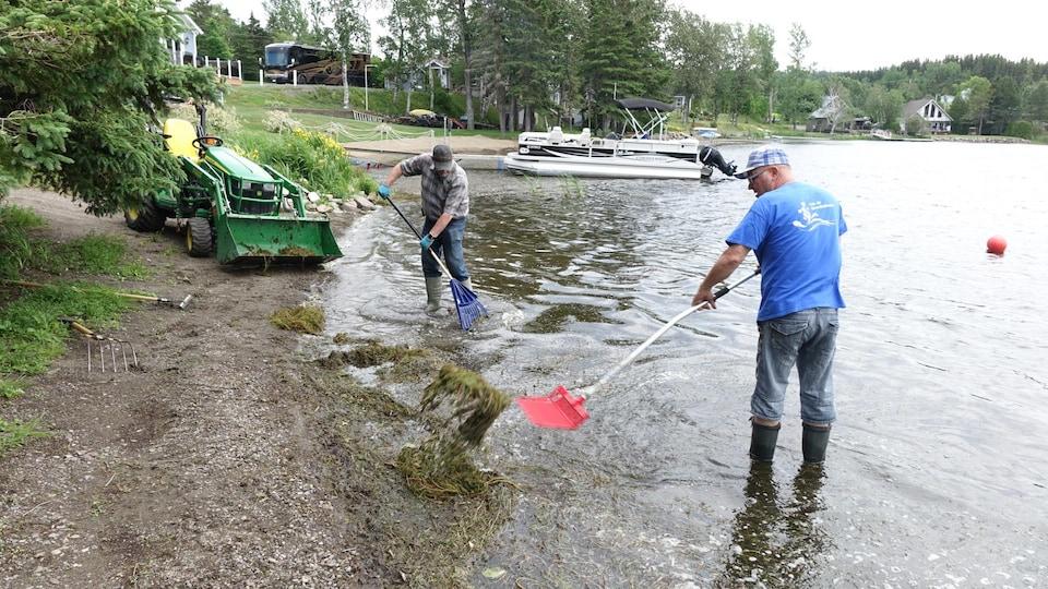 Deux hommes nettoient le lac du Gros Ruisseau.