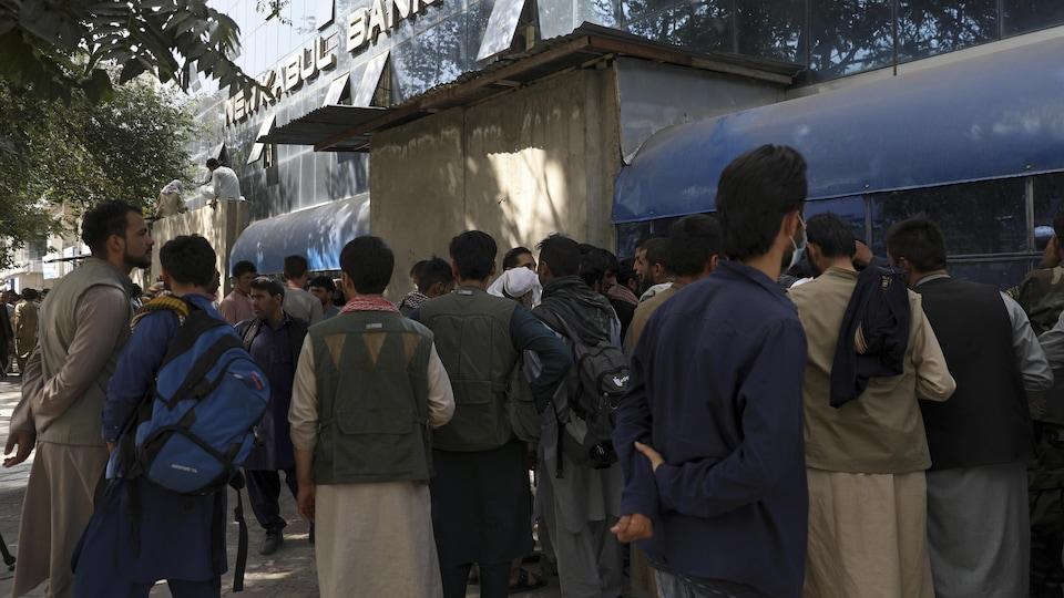 Des Afghans font la queue devant une banque de Kaboul.