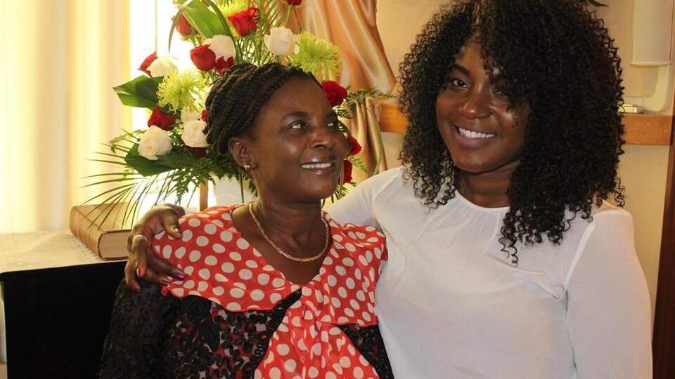 Nadège Civil et sa mère Danise Maurice devant des bouquets de fleurs.